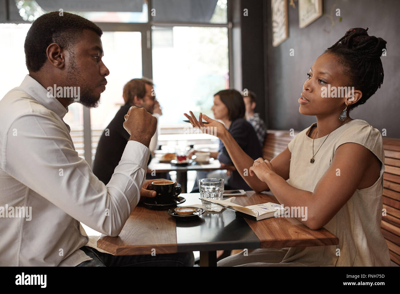 African woman and man discussing business ideas at busy cafe - Stock Image