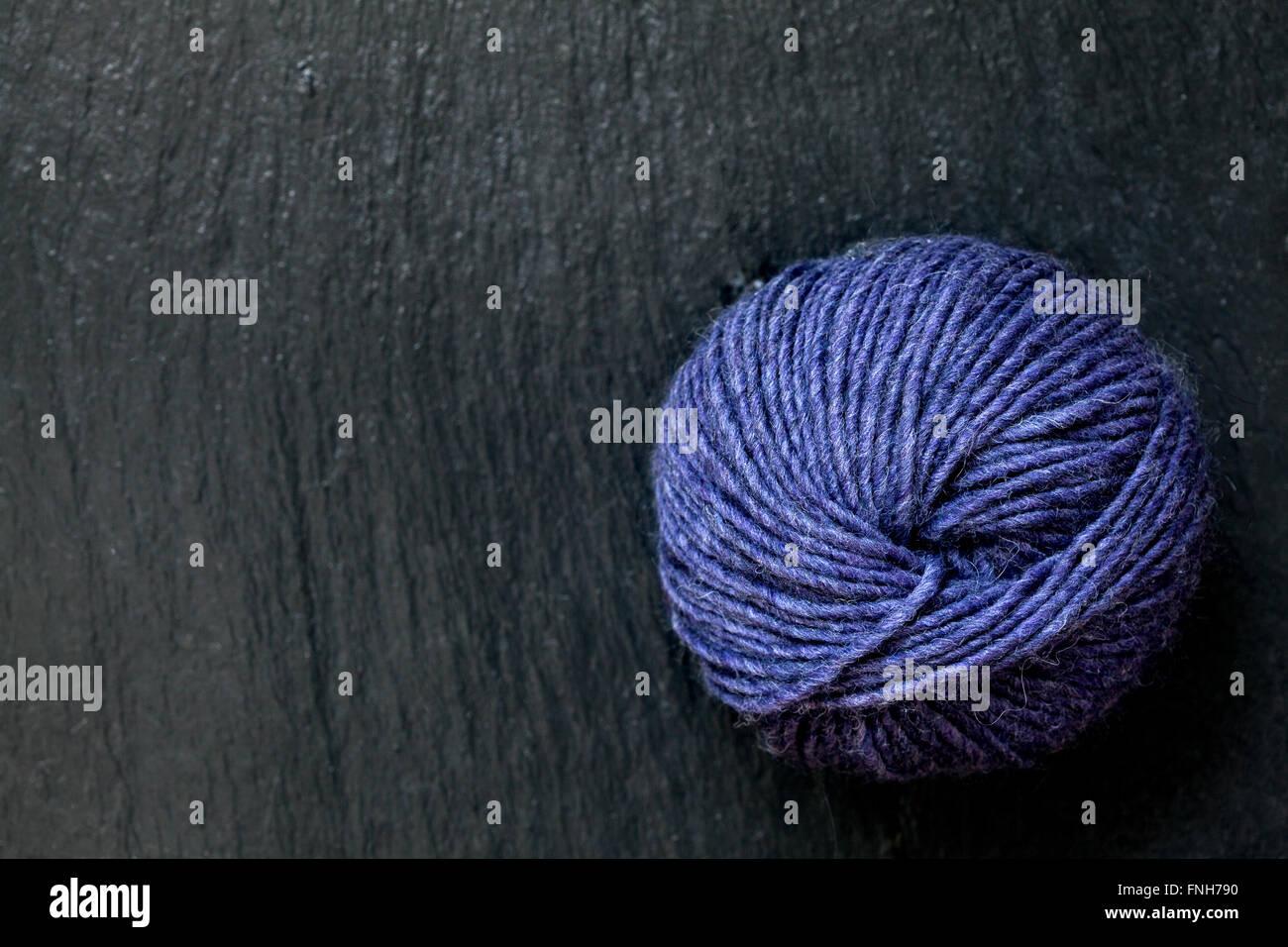 skein of purple yarn with black slate background - Stock Image