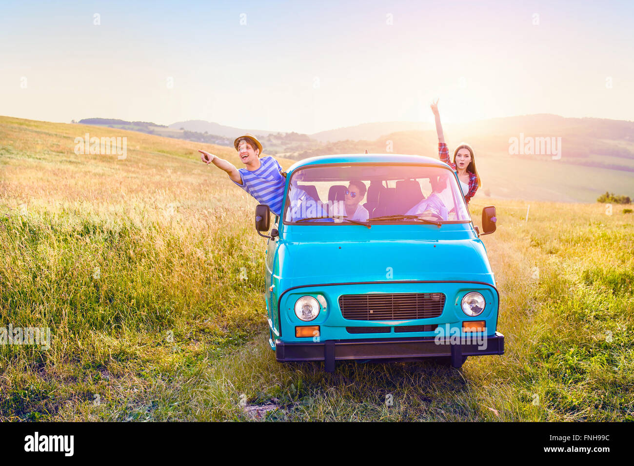 Young frieds leaning out of campervan, green sunny nature - Stock Image