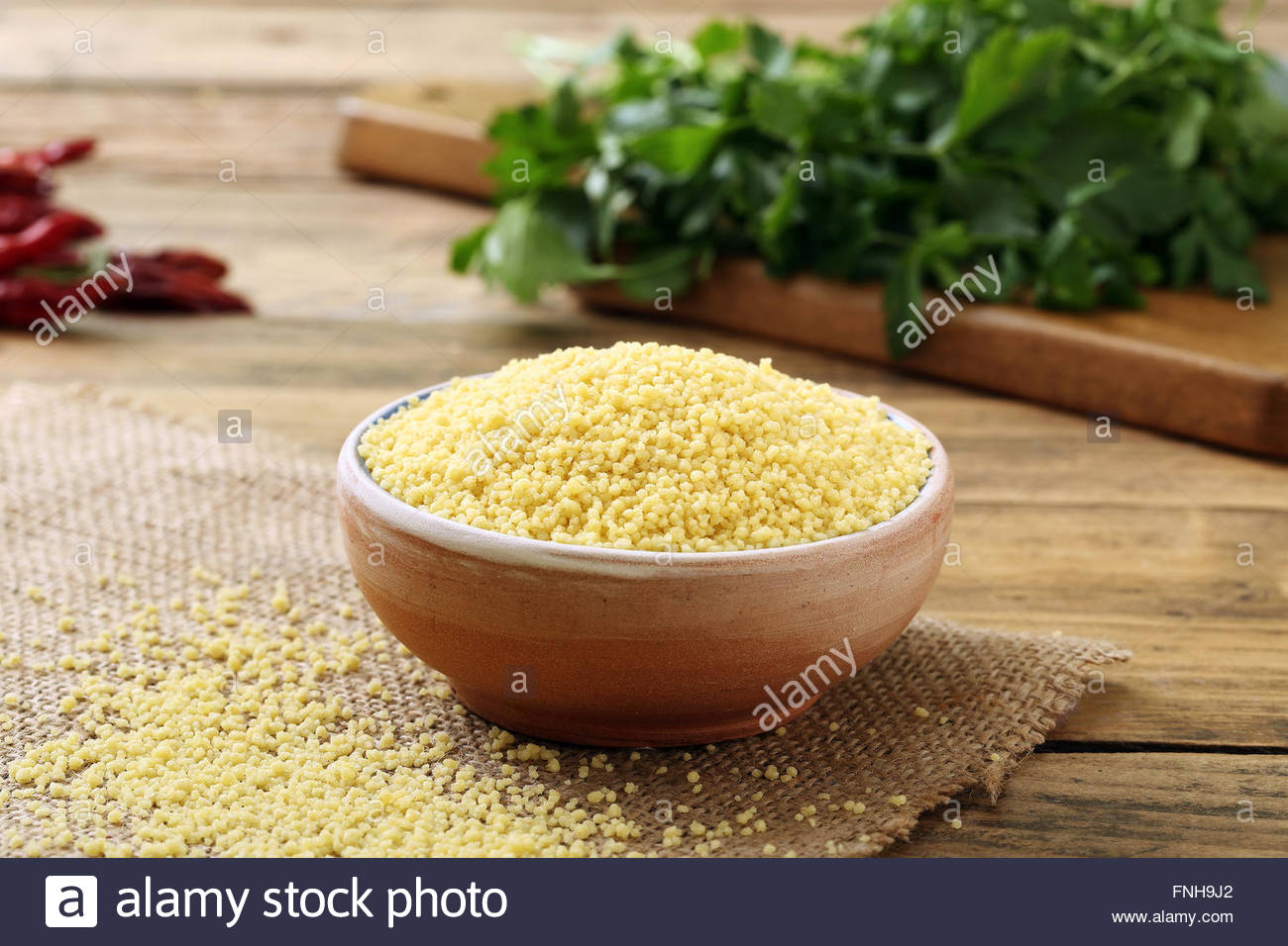 raw couscous in ceramic bowl on kitchen wooden table background - Stock Image
