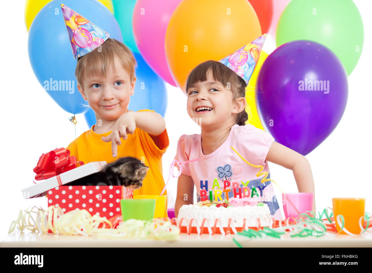 happy children celebrating birthday party with opening gift box - Stock Image