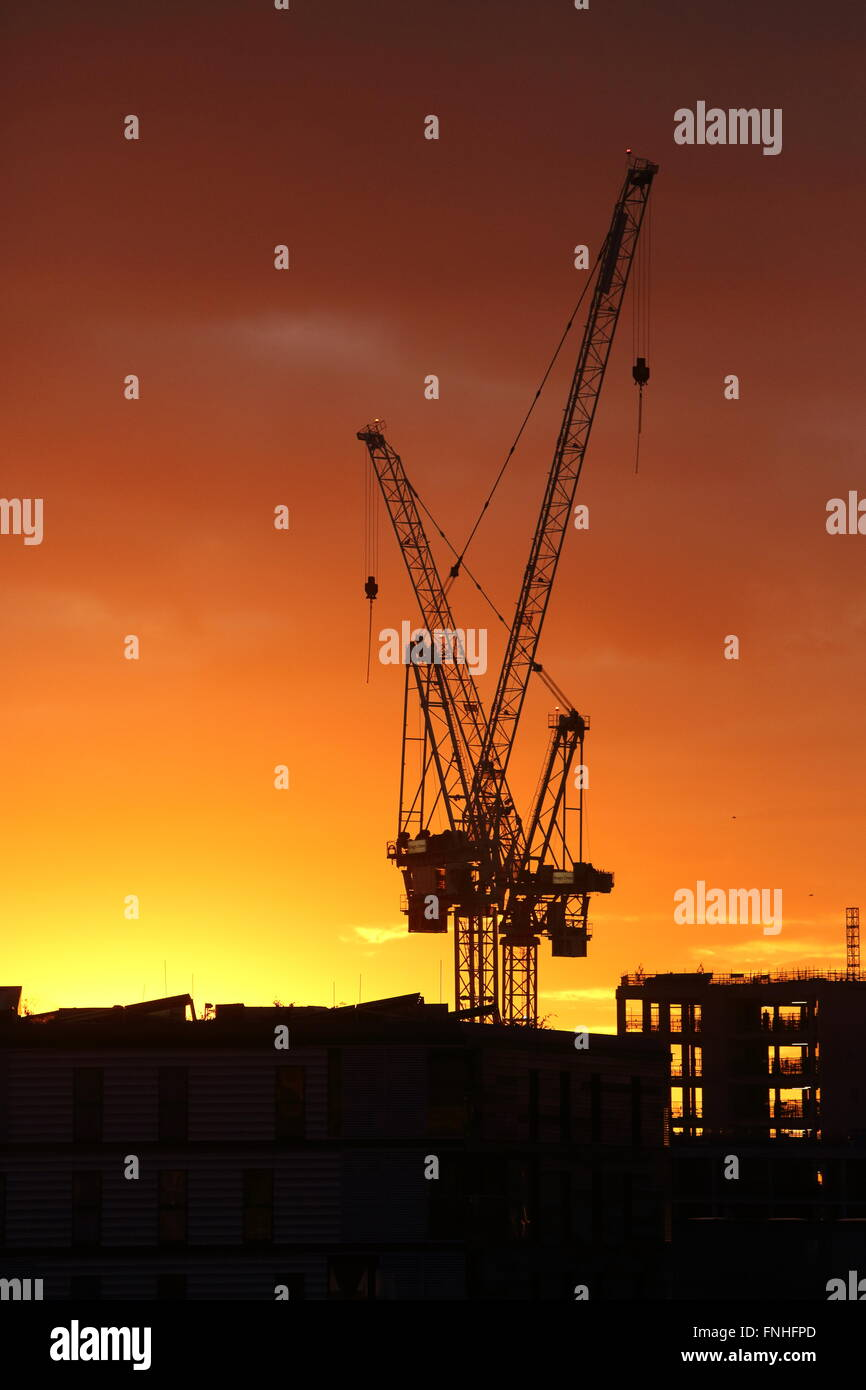 Silhouette of crane and construction work at sunset, at Kings Cross, north London, England, UK - Stock Image