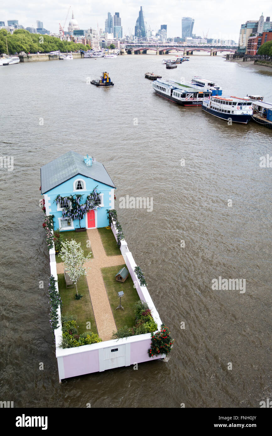 A single family house floating down the river thames in central London Stock Photo