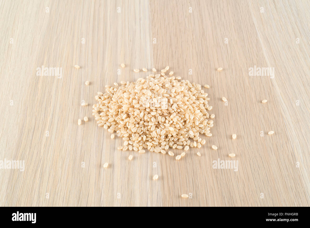 Brown rice on wooden table - Stock Image