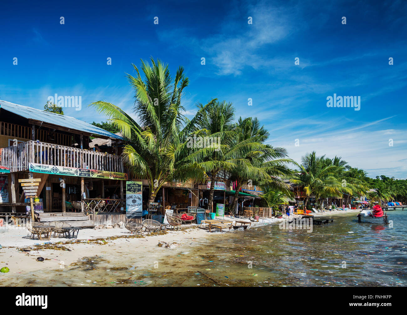 polluted dirty beach with garbage rubbish floating in sea on koh rong island cambodia - Stock Image