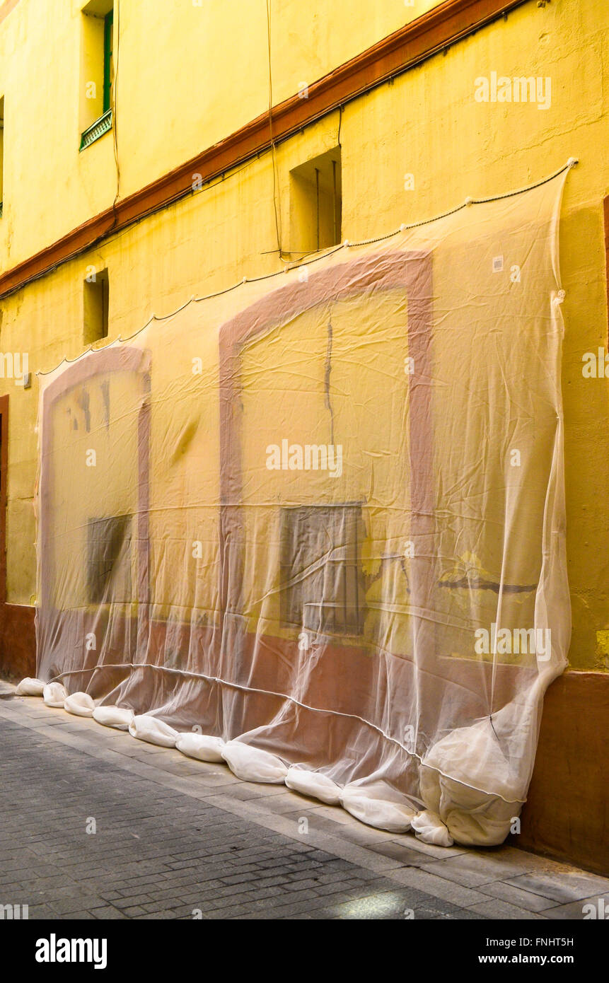 Protecting a wall in a street. Barcelona, Catalonia, Spain. - Stock Image