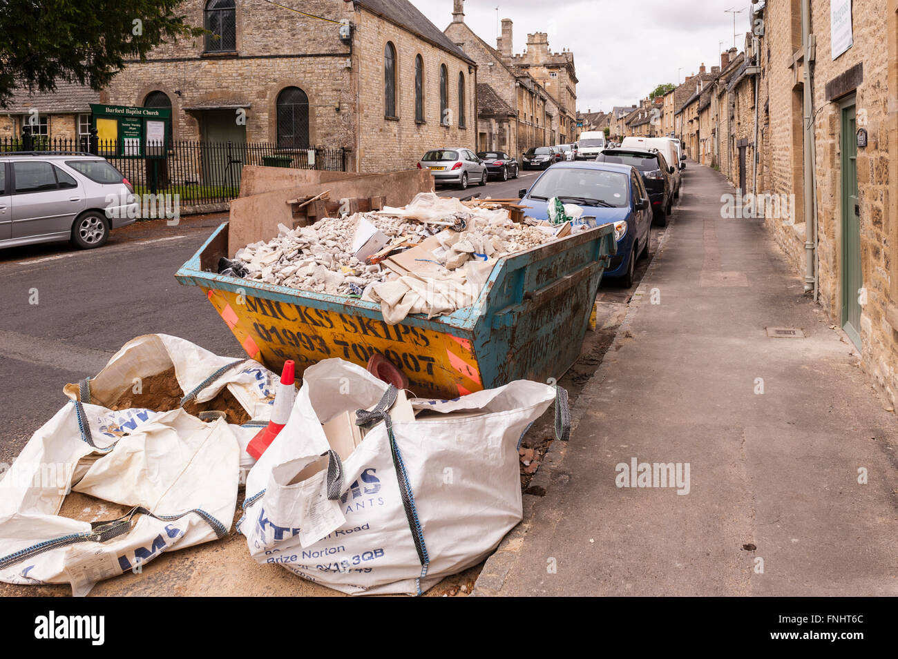 A builders skip spoils the view of the pretty Cotswold town of  Burford , Oxfordshire , England , Britain , Uk - Stock Image