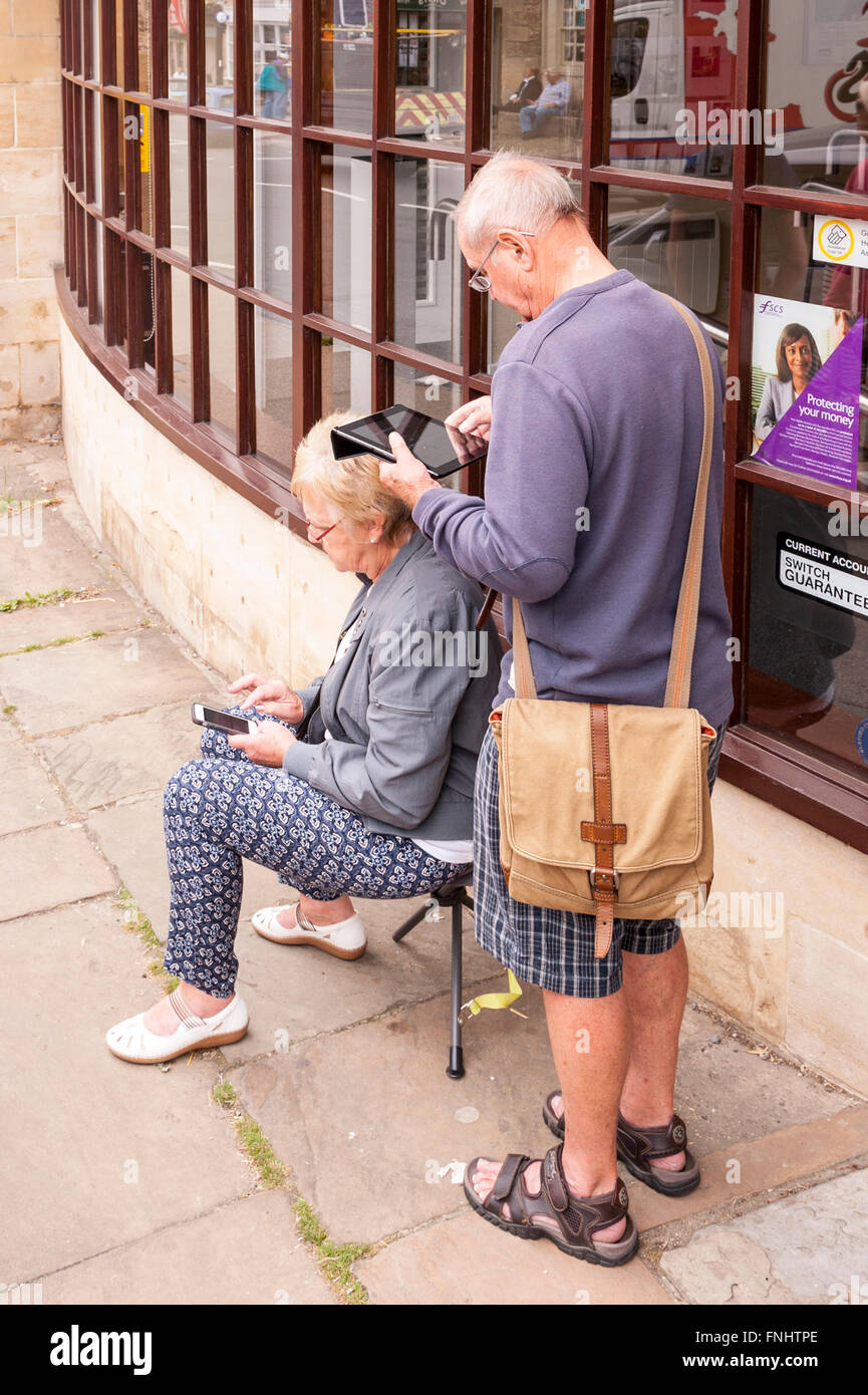 An elderley couple absorbed in their tablet and mobile phone gadgets in the Uk - Stock Image