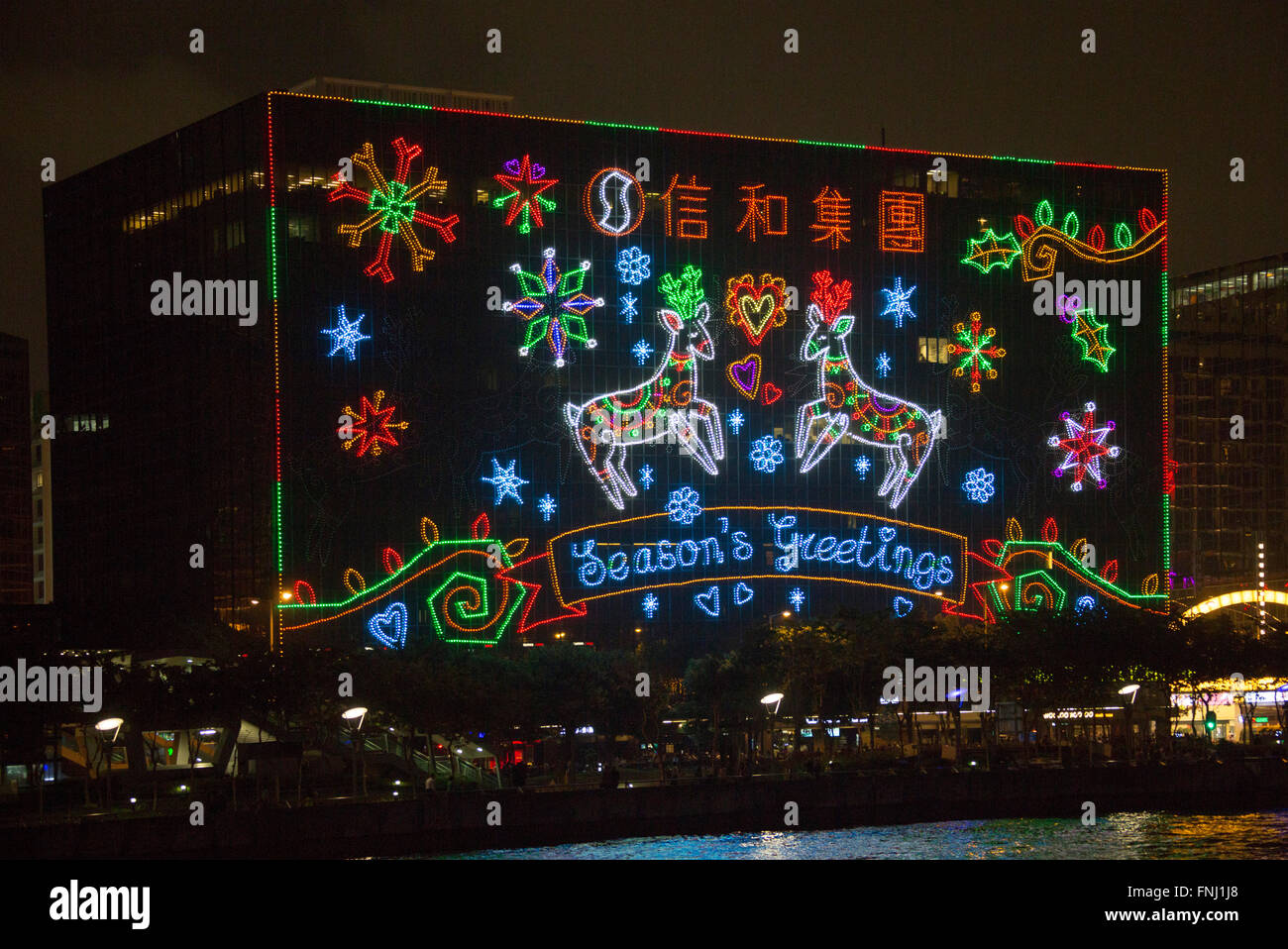 seasons greetings giant festive christmas lights display at night on buildings victoria harbour hong kong island