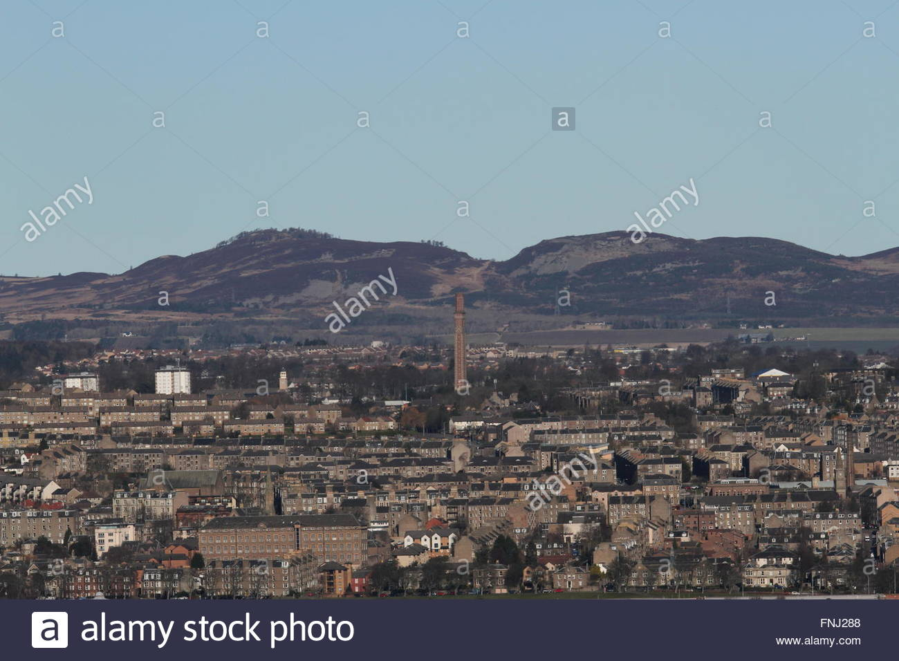 Cox's stack chimney and peaks of Auchterhouse and Balkello Hills viewed from Fife Scotland  February 2016 - Stock Image