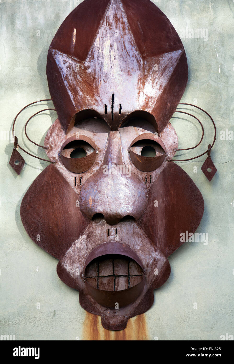 Metal Mask Sculpture on Wall in Cape Town - South Africa - Stock Image