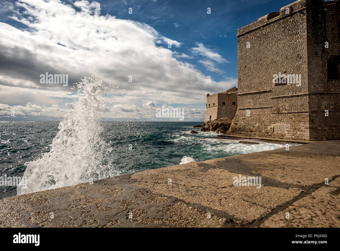 Waves splashing against the ancient city walls of the old city of Dubrovnik, Croatia. - Stock Image