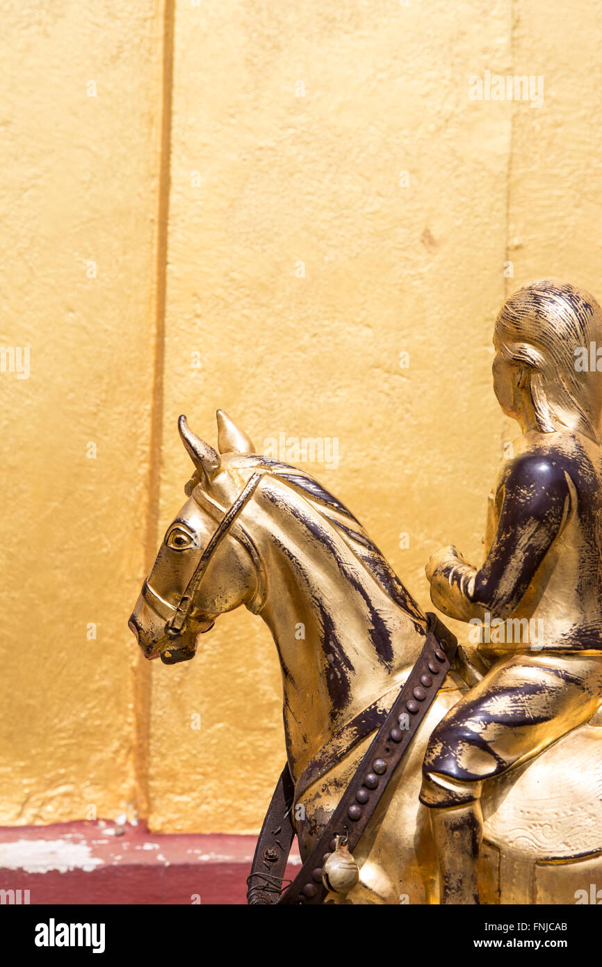 Golden sculpture statue of young girl riding a horse against gold ...