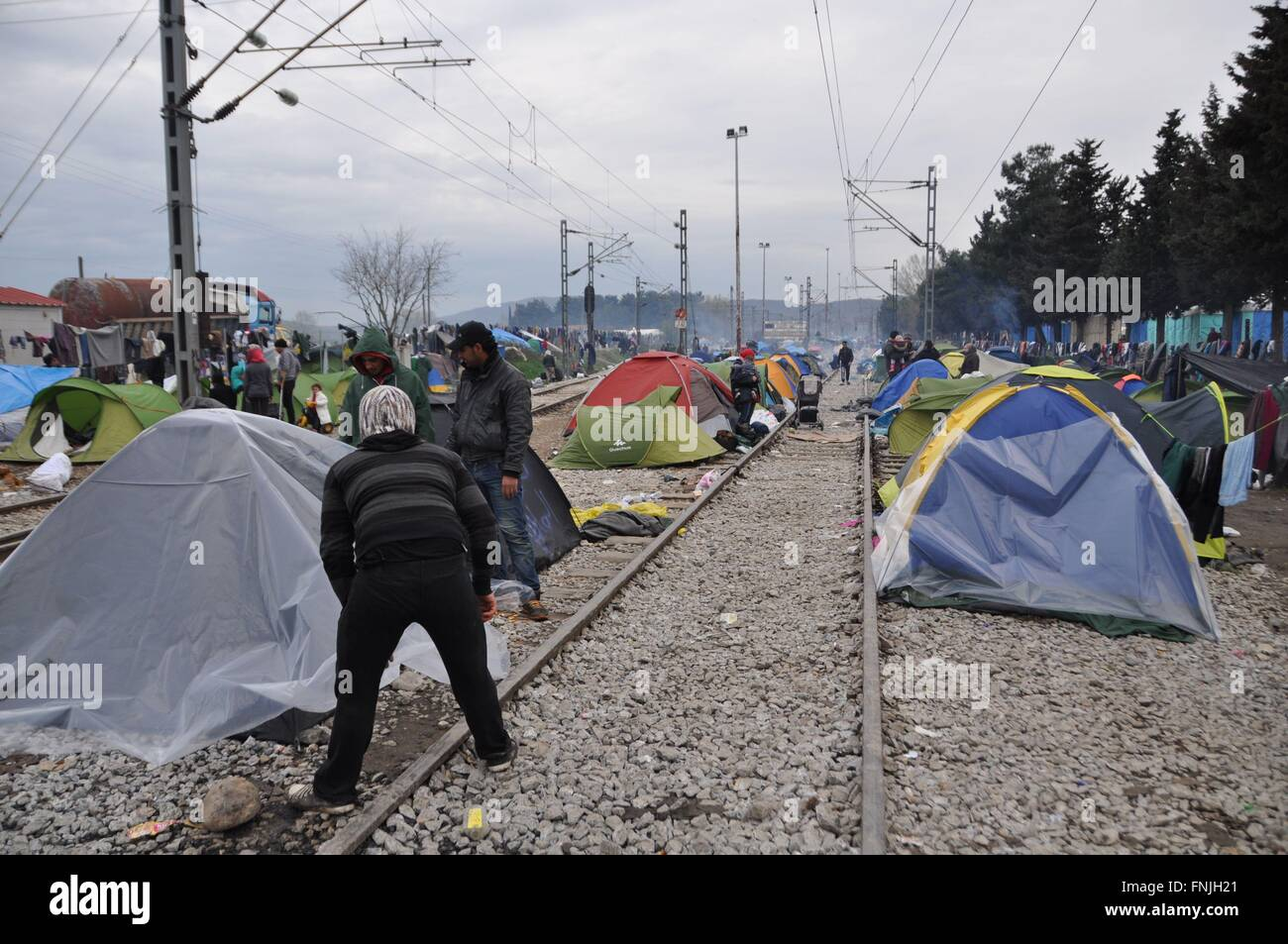 Idomeni, Greece. 14th Mar, 2016. Refugees put plastic on their tents at the Greek-Macedonian border near Idomeni, - Stock Image