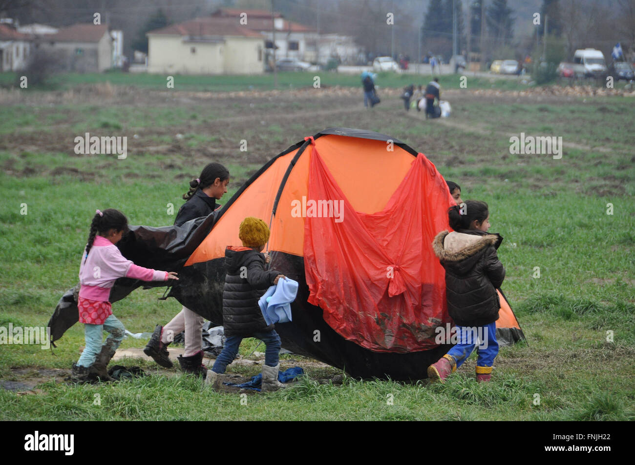 Idomeni, Greece. 14th Mar, 2016. Refugee children move their tent from mud at the Greek-Macedonian border near Idomeni, - Stock Image