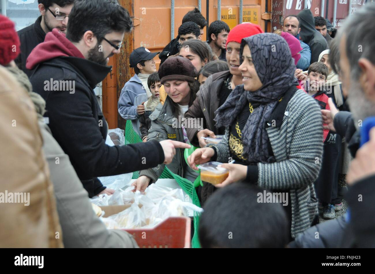 Idomeni, Greece. 14th Mar, 2016. Volunteers distribute hot soup and bread to the refugees at the Greek-Macedonian - Stock Image