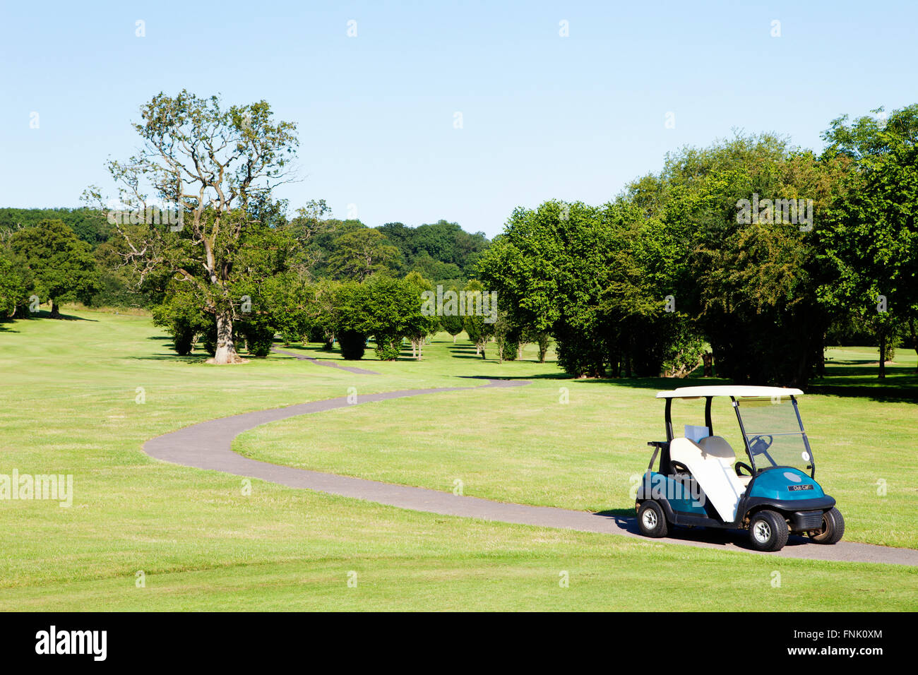 Empty golf buggy on path on a golf course - Stock Image