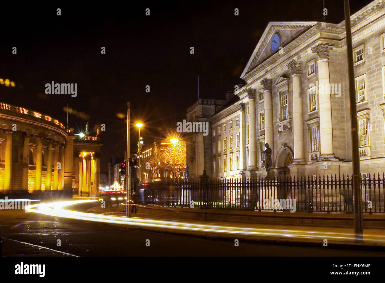 Car trails in front of Trinity College in Dublin city, Republic of Ireland at night - Stock Image
