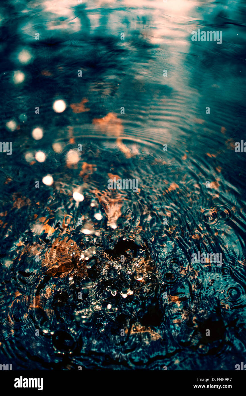 water droplets falling in to river - Stock Image