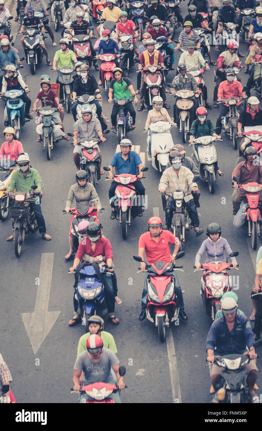 motorbike traffic in saigon - many scooter drivers , crowded street - Stock Image