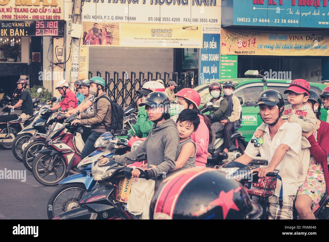 scooter driver waiting at traffic light , motorbike traffic , streets of saigon, vietnam - Stock Image