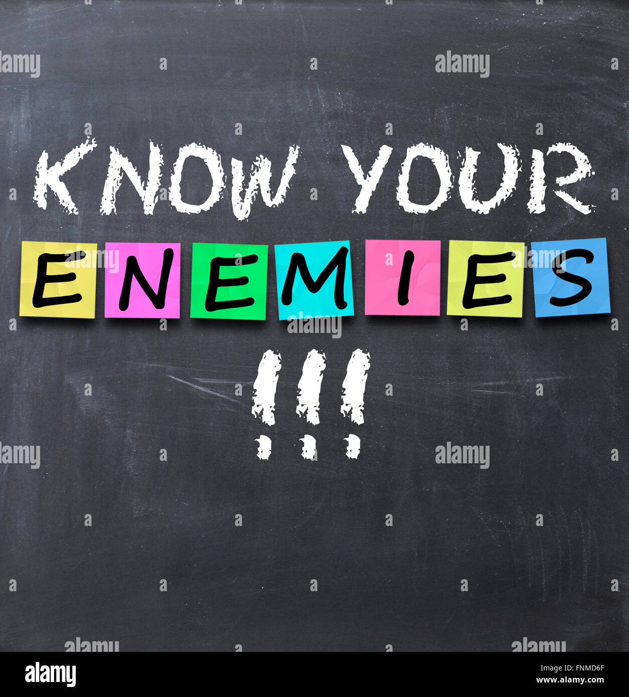 Know your enemies text on a blackboard with chalk and stickers - Stock Image