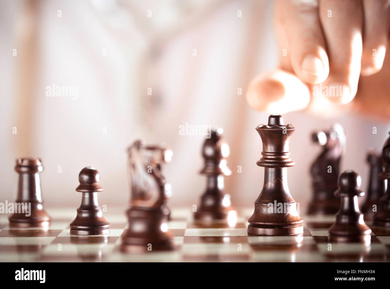 Board game, chess player hand about to play, excellence concept. - Stock Image