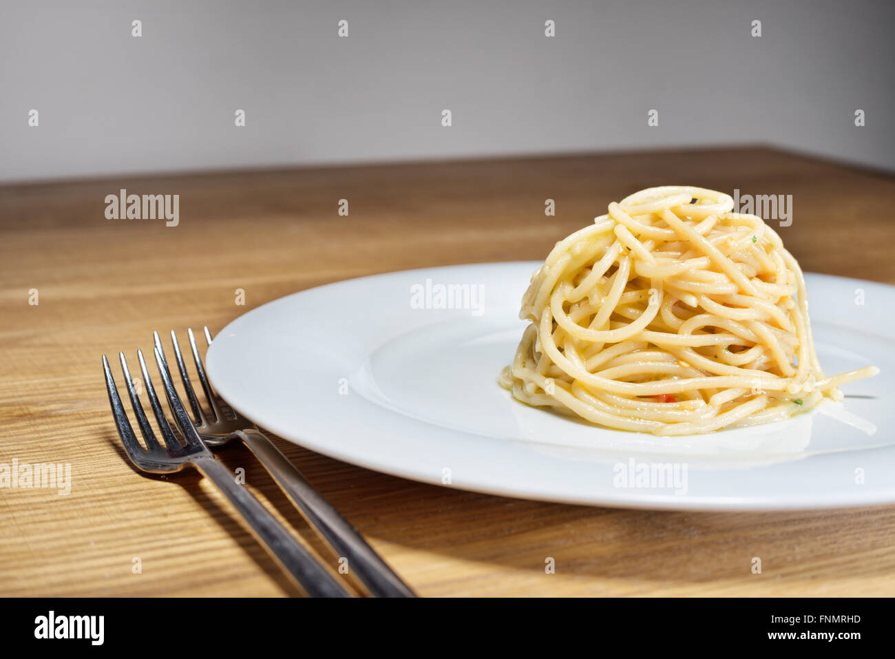 spaghetti with garlic, oil and hot peppers with parsley and fork on table - Stock Image