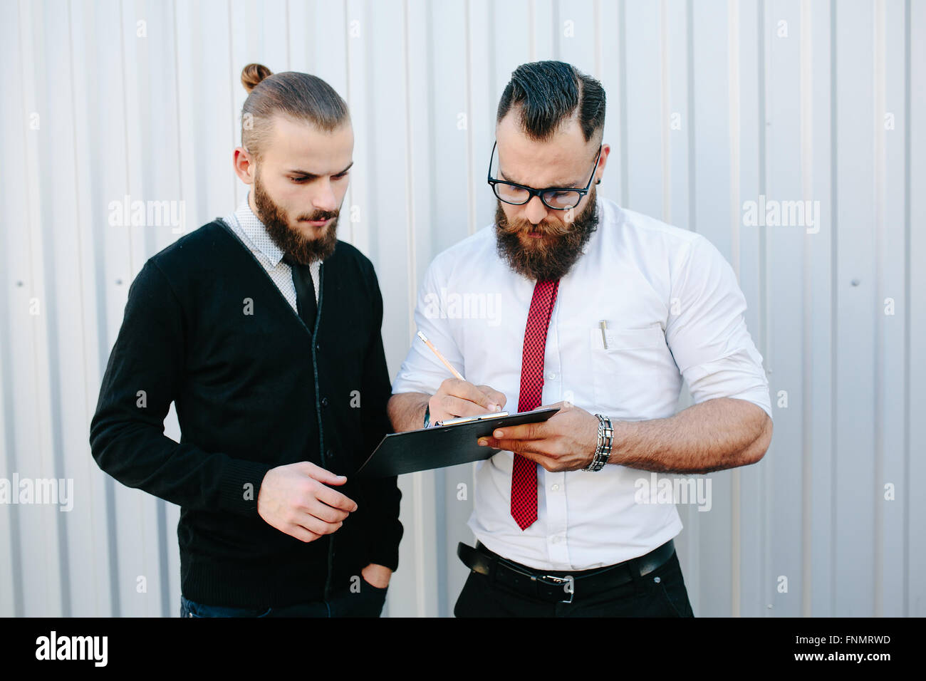 Two bearded businessman signing documents - Stock Image