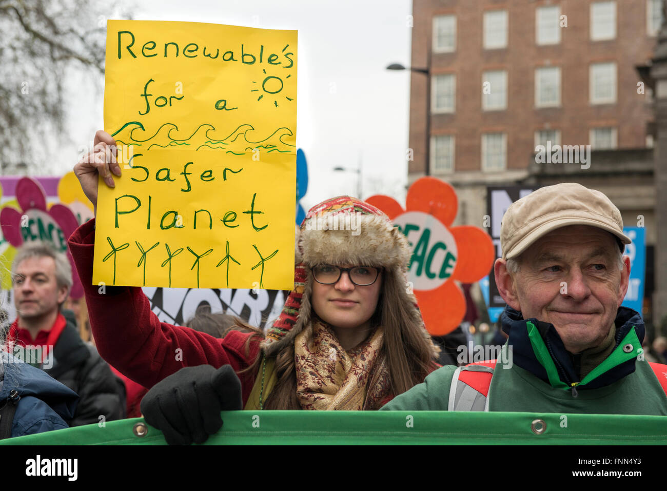 A young woman, Green Peace supporter, is holding a placard 'Renewable's for a Safer Planet' during the - Stock Image