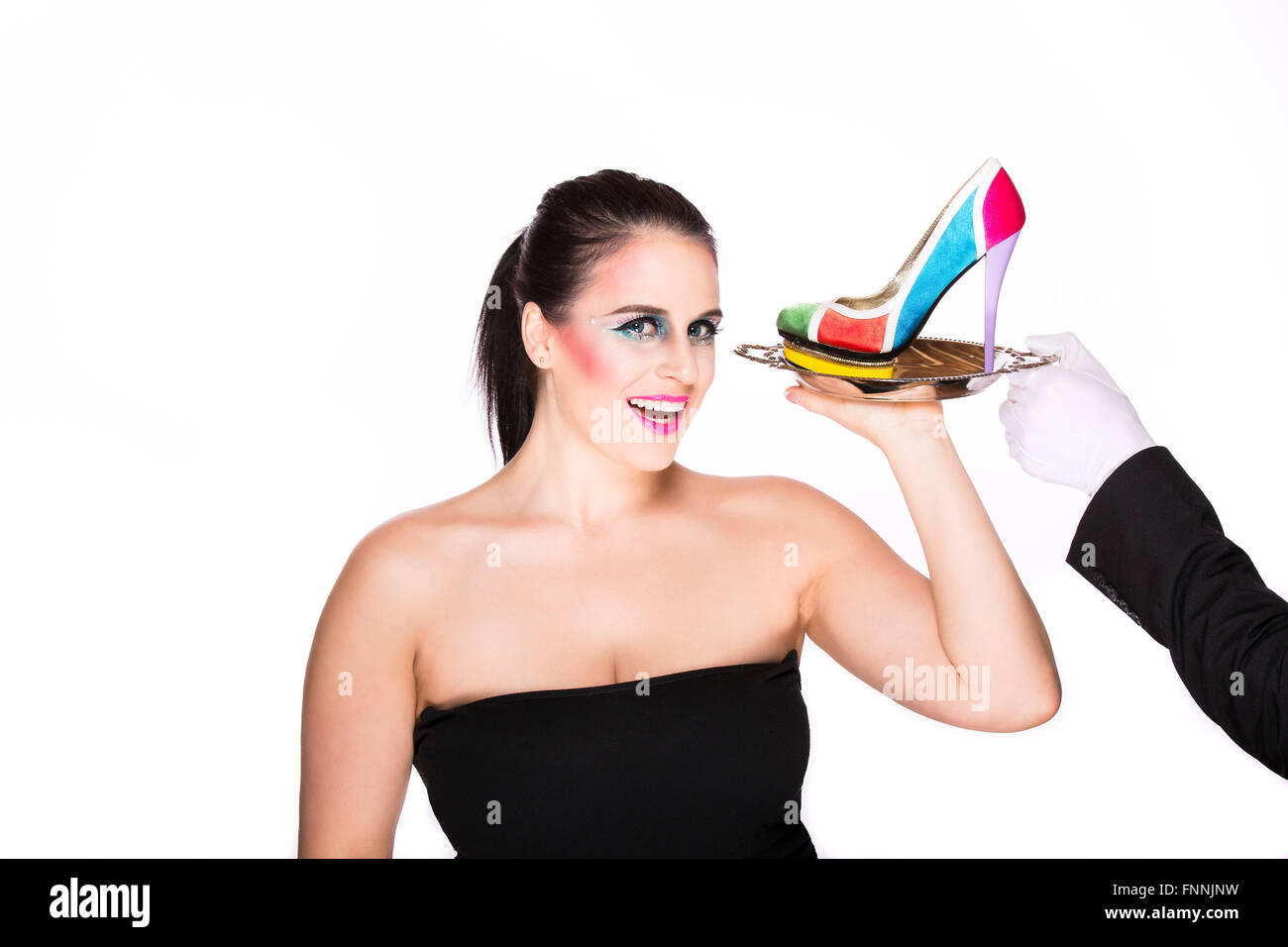 Smiling brunette holding a very colorful stiletto shoe on a silver platter being offered to her by a butler - Stock Image
