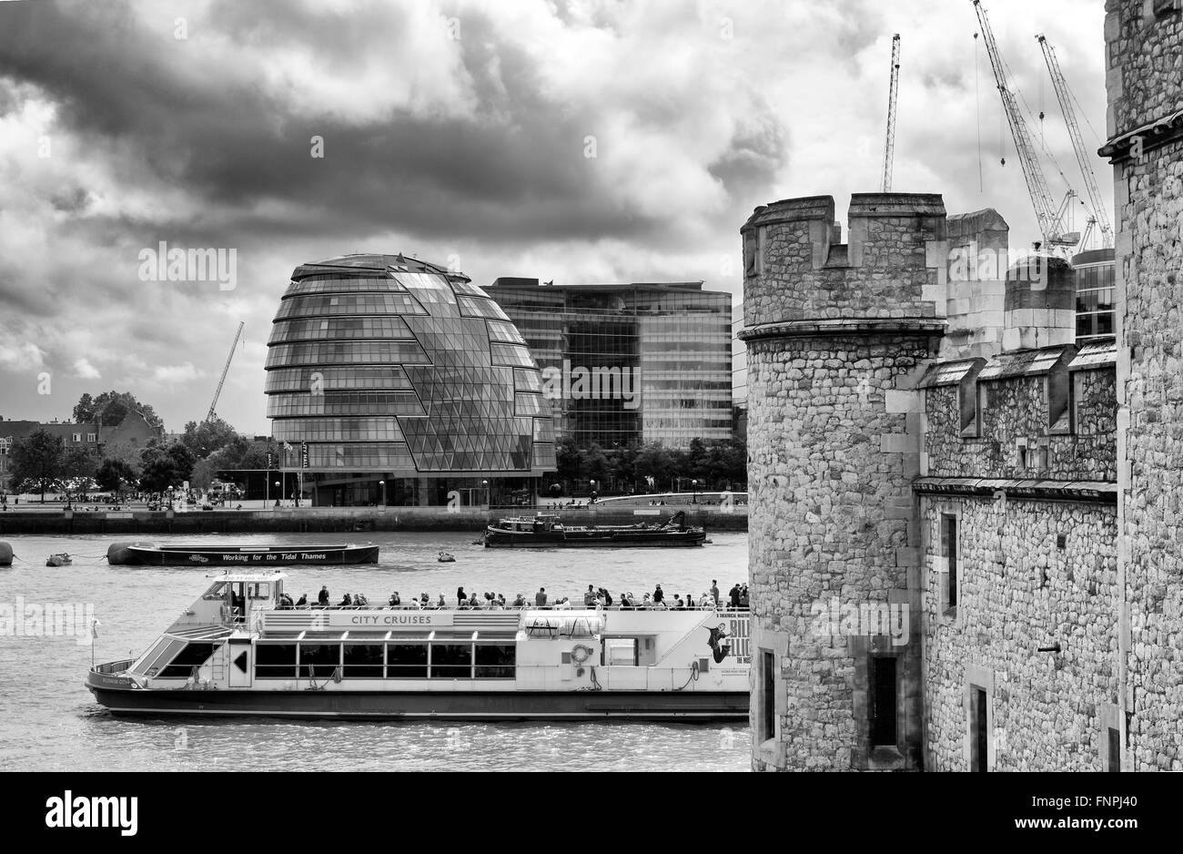 Thames River scene showing London City council offices, tour boat, tower of London on a rainy day in winter - Stock Image