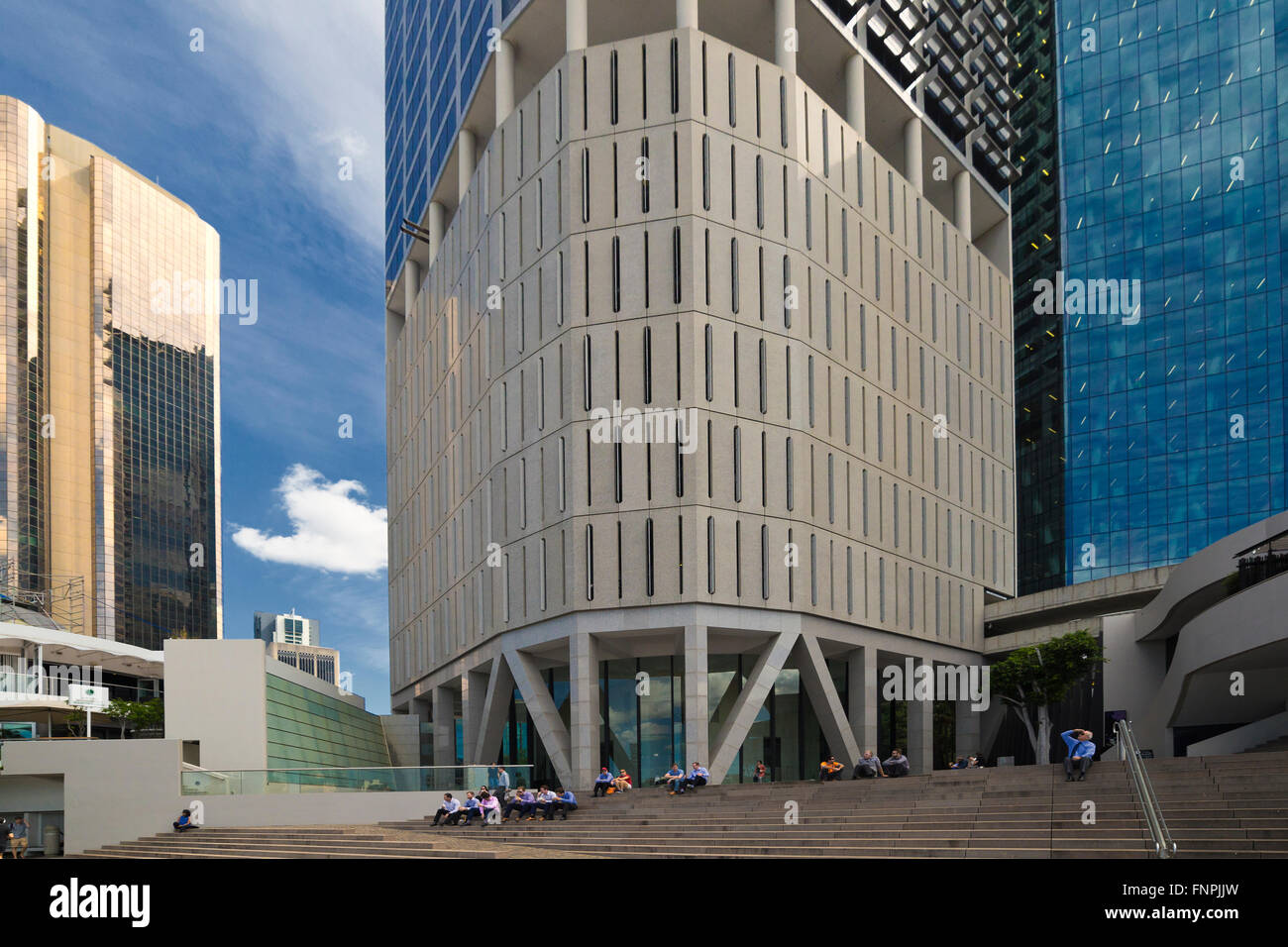 White collar office workers take lunch overshadowed by the high rise office blocks in Brisbane, Queens central business - Stock Image