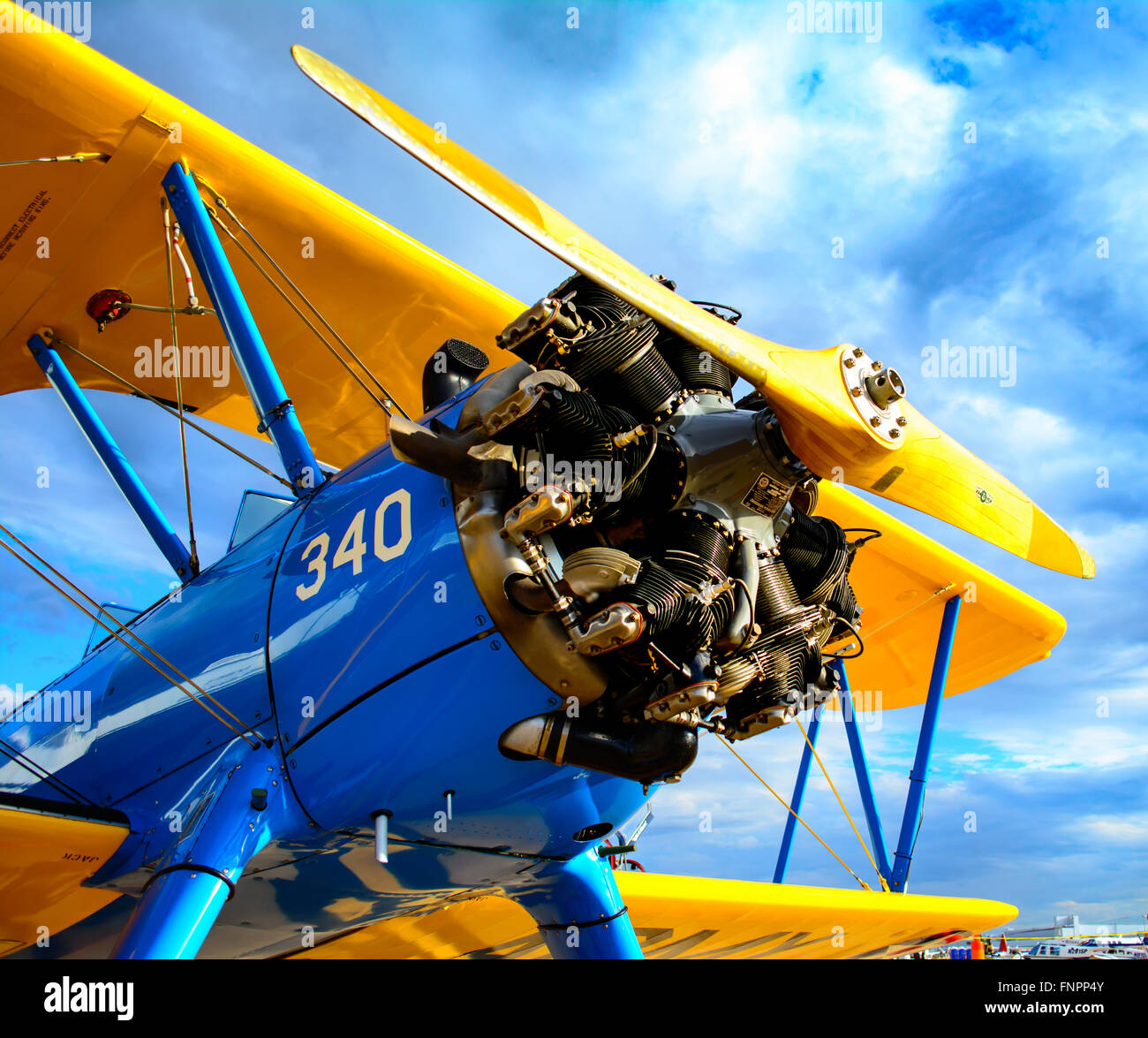 Blue and Yellow Biplane against blue sky - Stock Image