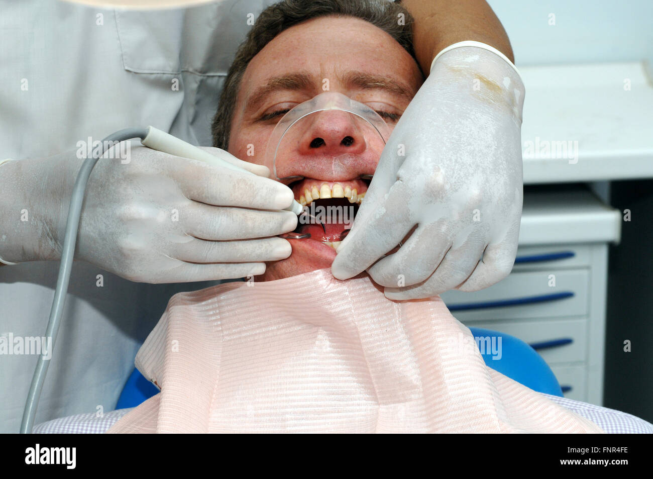 A dentist removing plaque and tartar from a man's teeth to prevent cavities and other peridontal problems - Stock Image