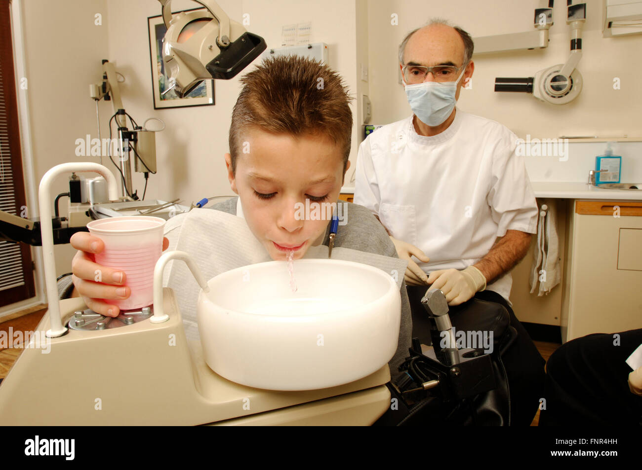 A young boy rinsing his mouth with anti-microbial solution watched by his dentist. - Stock Image