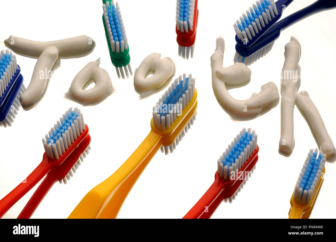 """The word """"tooth"""" is written out using toothpaste on a mirrored surface, surrounded by multicouloured toothbrushes. Stock Photo"""