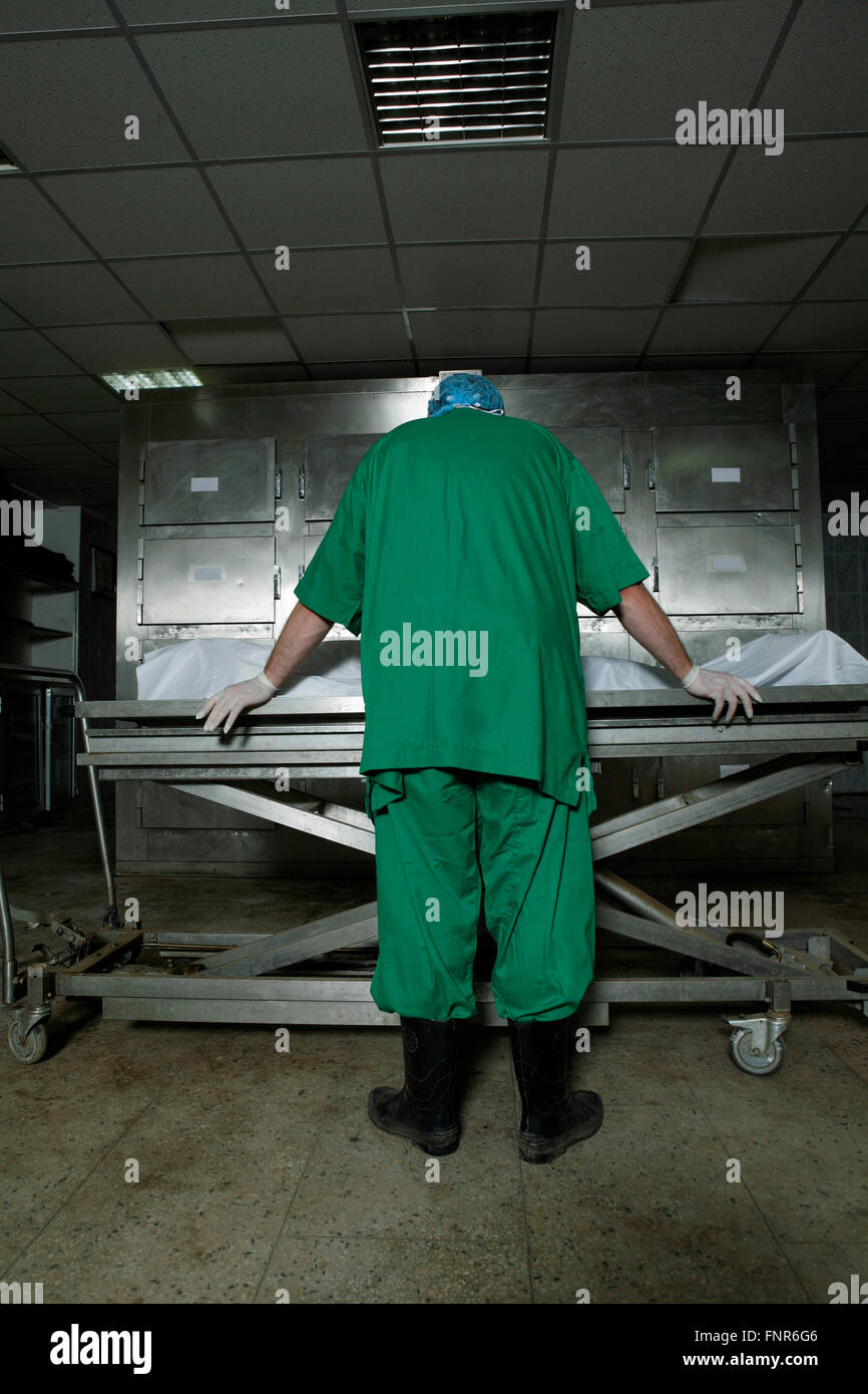 A pathologist leans over a corpse on a operating trolley awaiting examination. - Stock Image