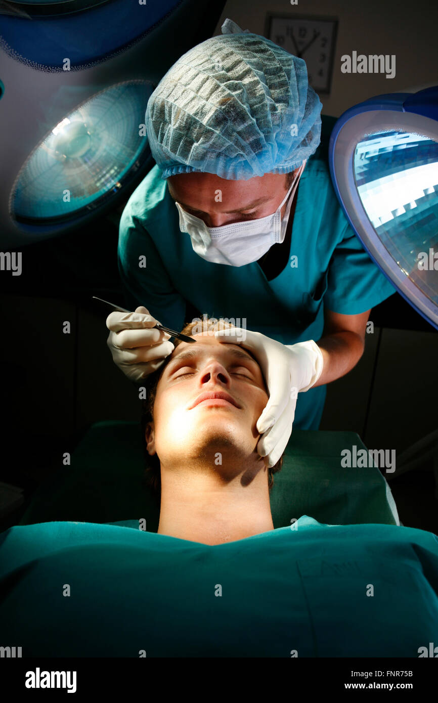 A surgeon prepares to make a surgical incision into the forehead of a patient. - Stock Image