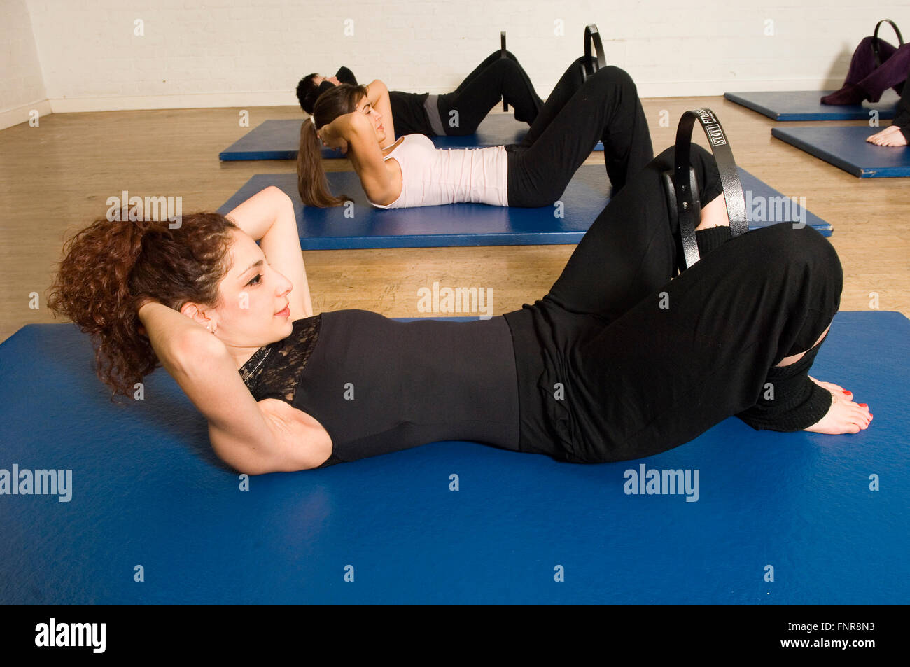Pilate's Curl Up position using an inner thigh squeezing fitness. - Stock Image