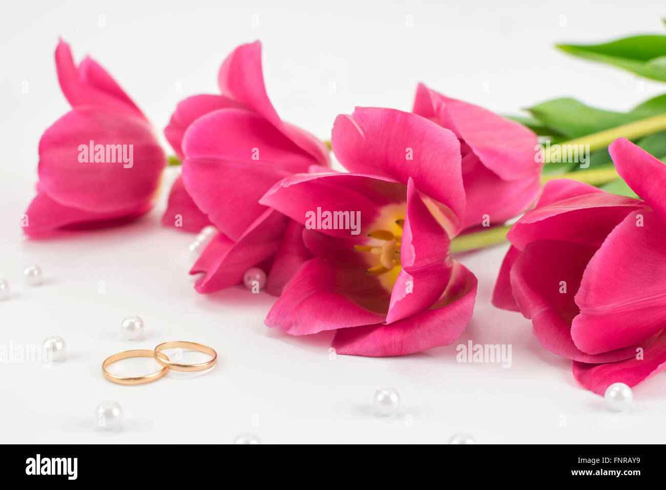bouquet of red tulips, wedding rings, perfume and bead lying on a white background - Stock Image