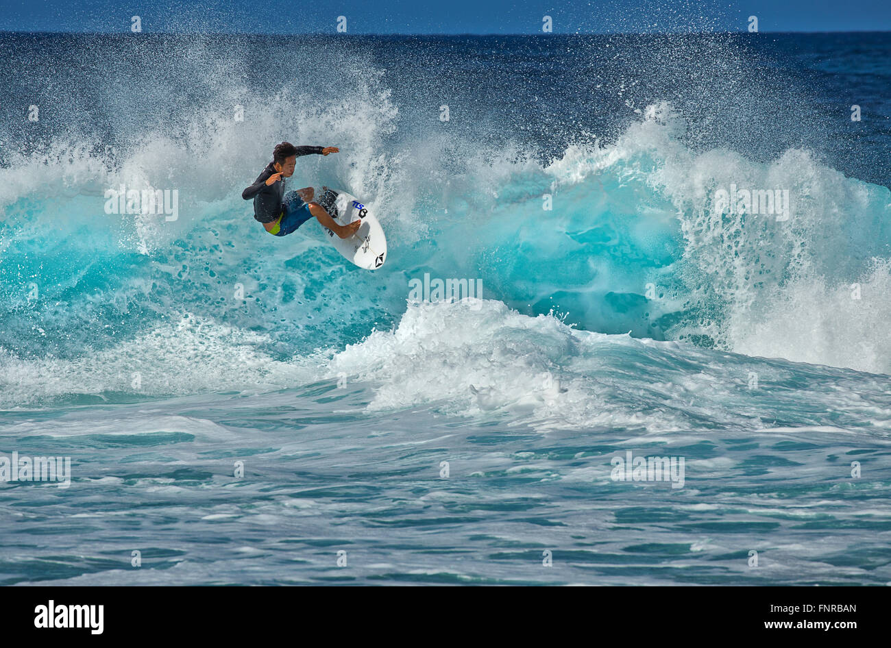 A surfer tackles the notoriously difficult Pipeline surf break. in Oahu, Hawaii. - Stock Image