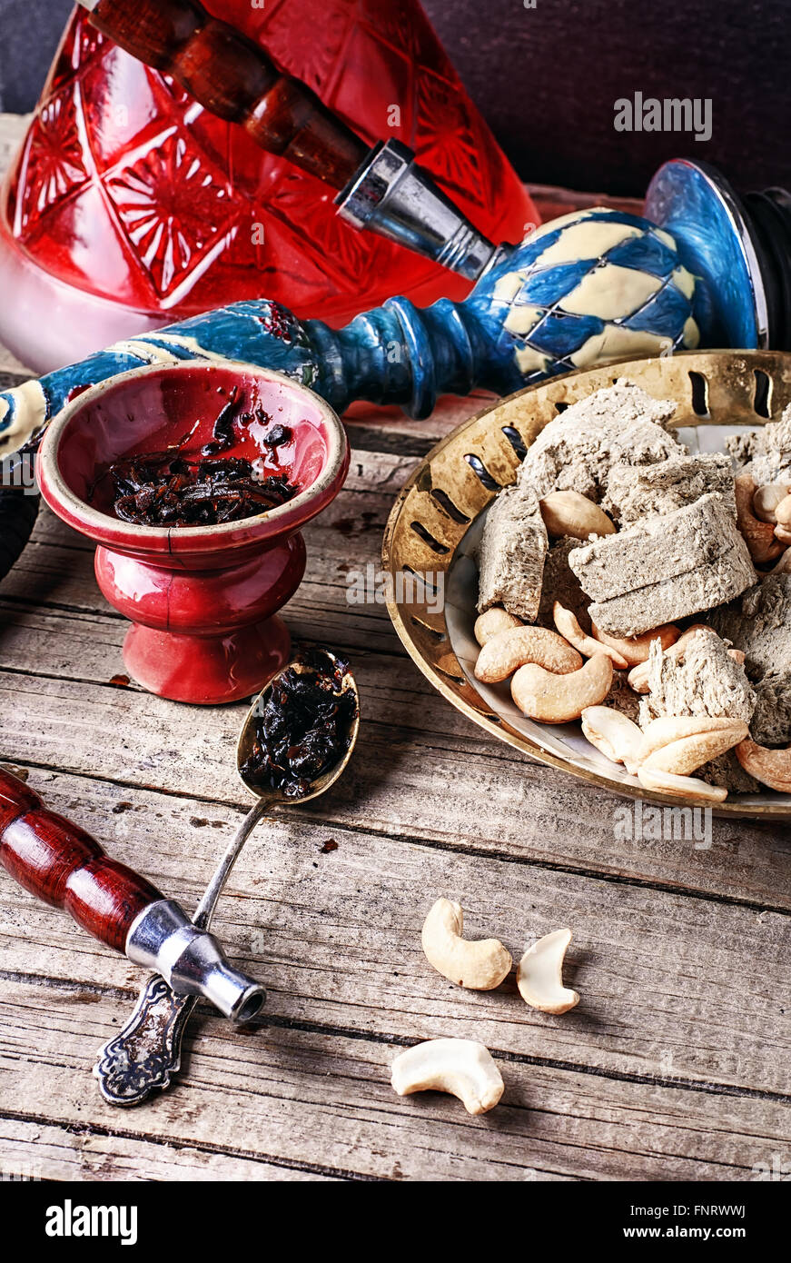 Composition with smoking hookah,tobacco and a plate of halva and cashews - Stock Image