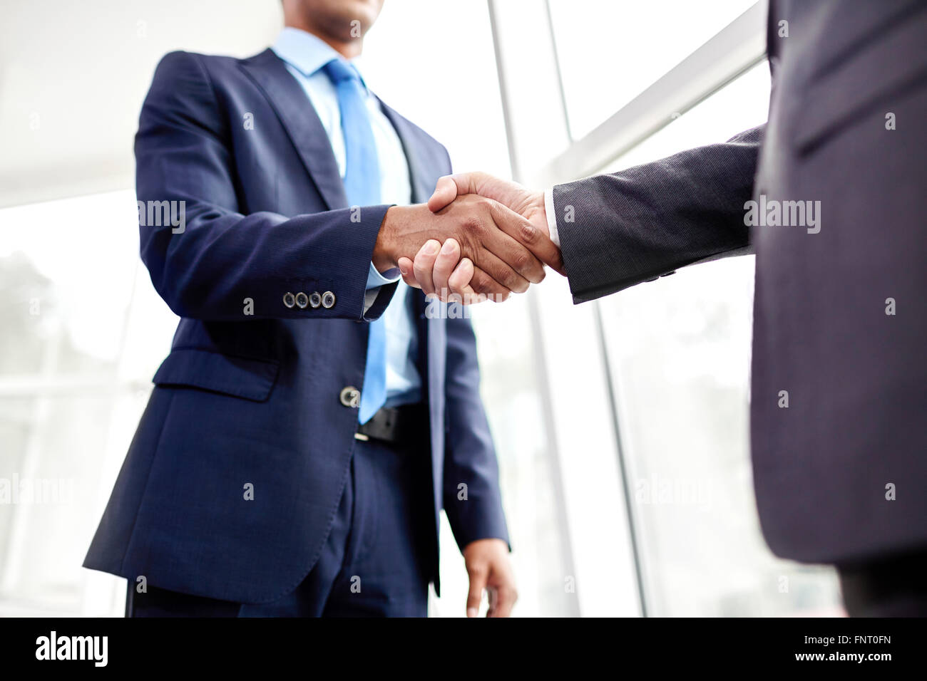 Handshake of two business people in the office - Stock Image