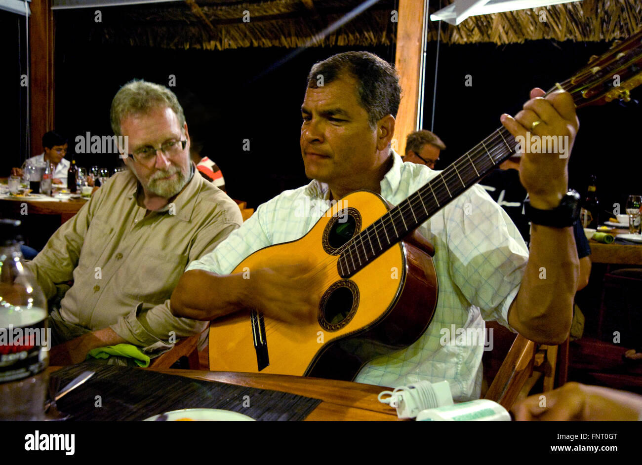 President Rafael Correa of Ecuador serenades show host Peter Greenberg and his crew during dinner after day of filming - Stock Image