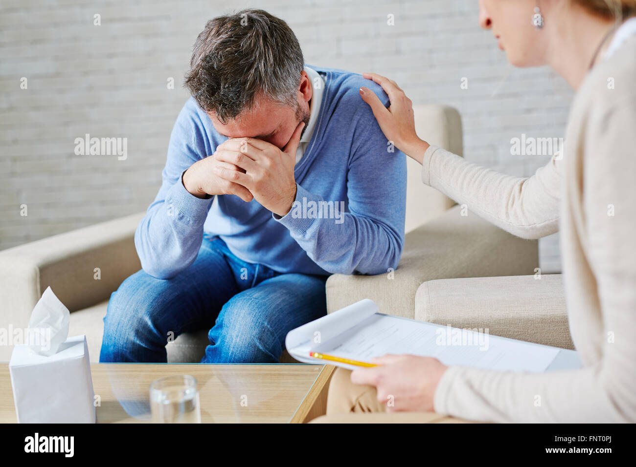 Hopeless man visiting psychologist - Stock Image