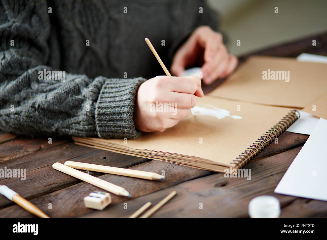Close-up of male hands drawing in notebook - Stock Image
