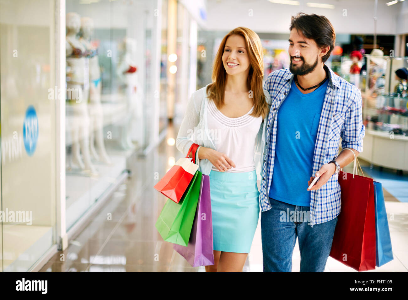 a3e8ae0032 Happy couple walking in the store with shopping bags Stock Photo ...