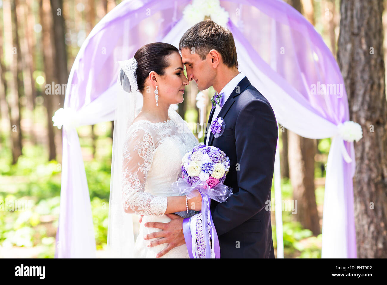 Bride and Groom Under Archway Stock Photo