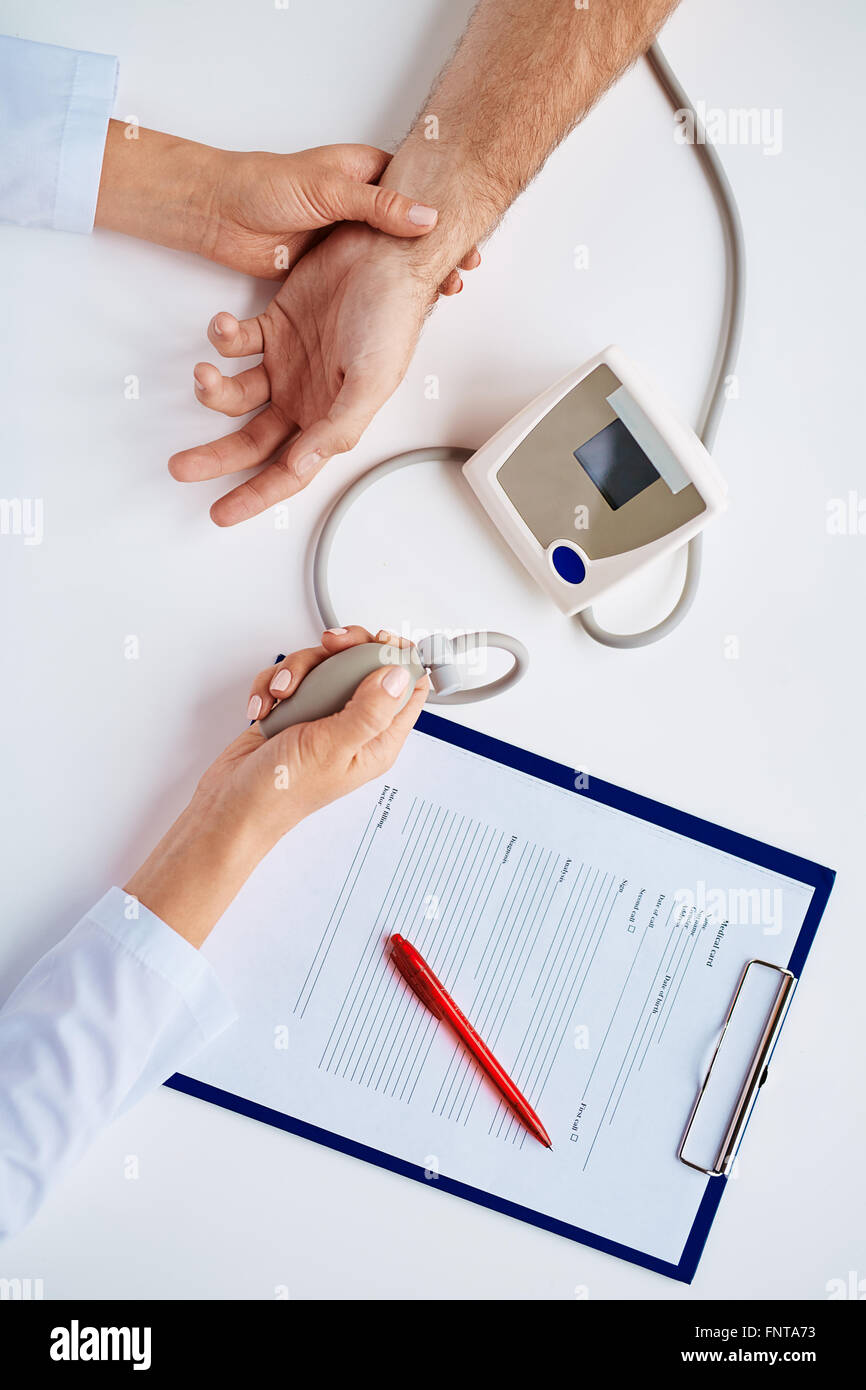 Hands of therapeutist with tonometer measuring blood pressure of patient - Stock Image